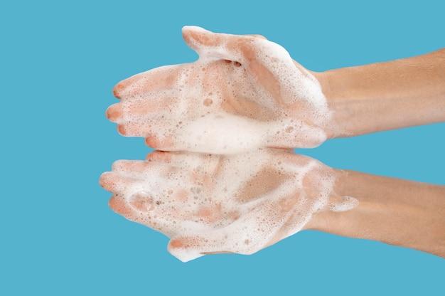 青色の背景で手を洗うトップビュー人 無料写真