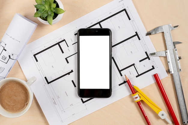 Top view phone on top of architectural plan Free Photo