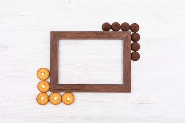Top view photo frame with cookies and copy space on white surface Free Photo