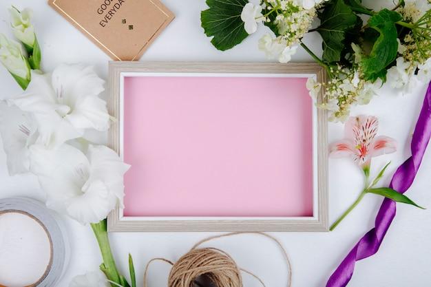 Vista dall'alto di una cornice con foglio di carta rosa piccola cartolina cartolina e fiori di colore bianco gladiolo e un ramo di viburno in fiore su sfondo bianco Foto Gratuite
