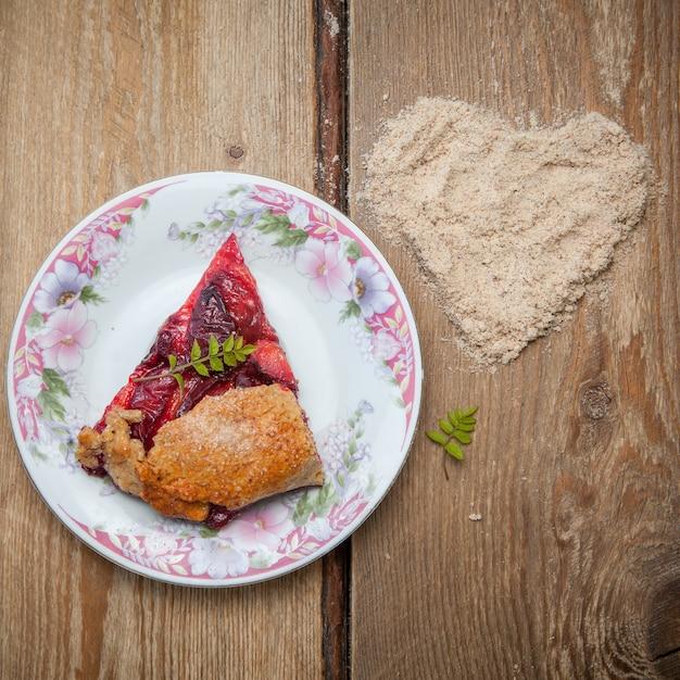 Вид сверху кусочек клубничного пирога с ореховыми крошками и сердечком в круглой цветочной тарелке Бесплатные Фотографии