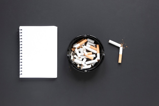 Top view pile of cigarettes with notebook Free Photo