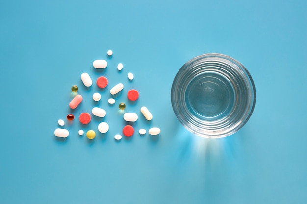 Top view of pills in triangle shape with glass of water Free Photo