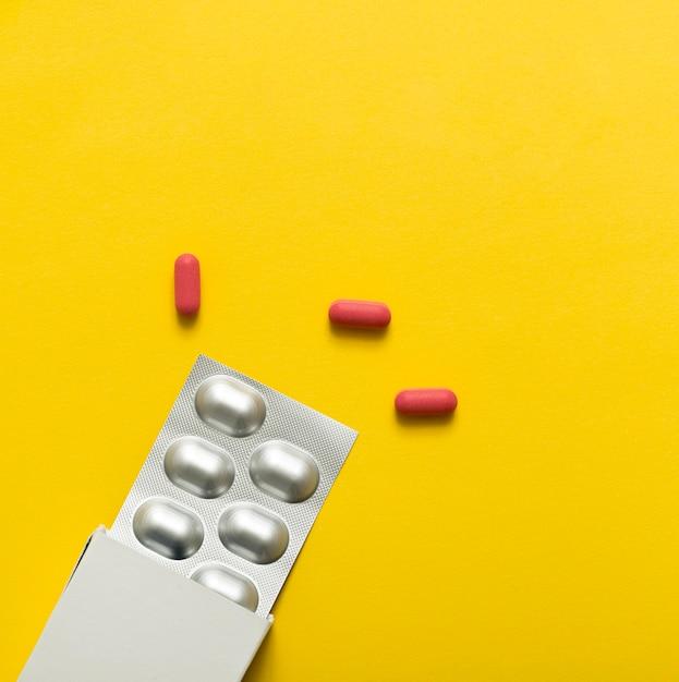 Vista dall'alto di pillole con pellicola e scatola Foto Gratuite