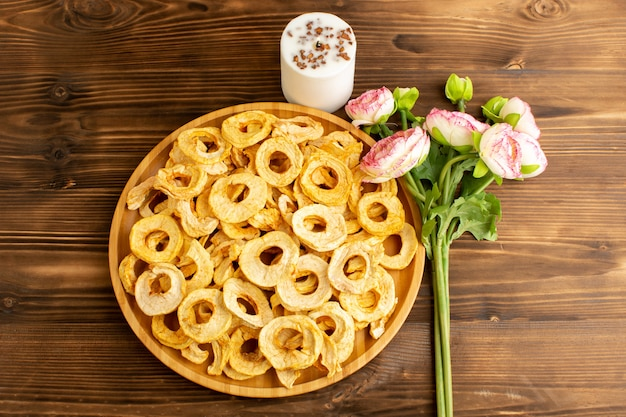 Una vista dall'alto ananas essiccato anelli all'interno del piatto secco frutta aspro gustoso gusto unico insieme a fiori rosa sulla scrivania in legno marrone frutti esotici secchi Foto Gratuite