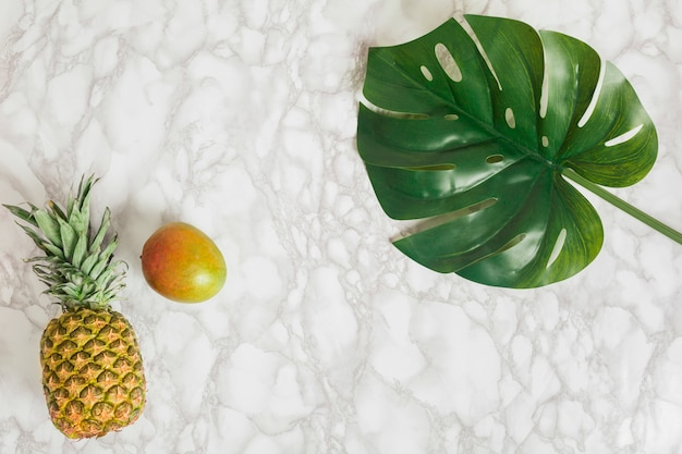 Top view pineapple, mango and tropical leaf Free Photo