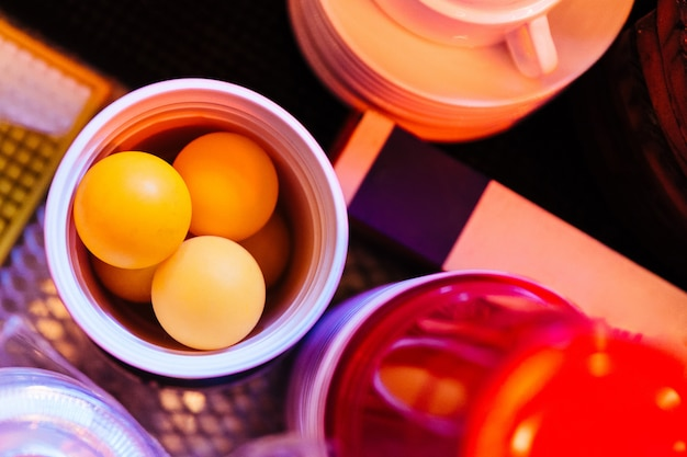 Top View Of Ping Pong Orange Balls Inside Red Beer Glass For