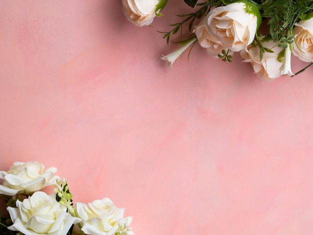 Top view pink background with white roses frame Free Photo