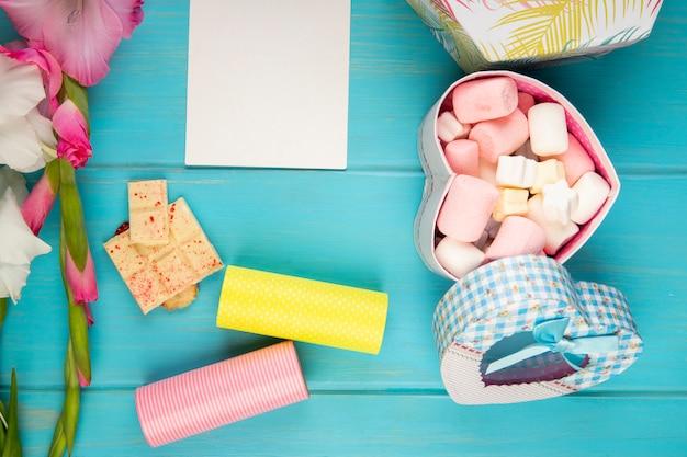 Vista dall'alto del fiore di gladiolo di colore rosa con rotolo di nastro adesivo, foglio di carta bianco, barretta di cioccolato bianco e confezione regalo colorata riempita con marshmallow sul tavolo blu Foto Gratuite