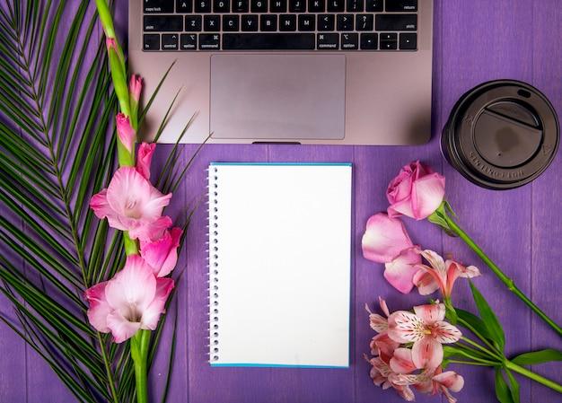Vista dall'alto di colore rosa gladiolo e rose con fiori di alstroemeria disposti intorno a un computer portatile sketchbook e una tazza di caffè di carta su sfondo viola Foto Gratuite