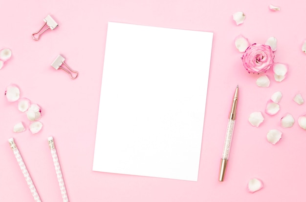 Top view of pink office supplies with rose petals Free Photo