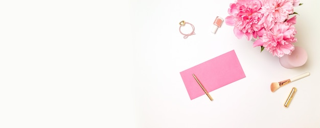 Top view of a pink paper envelope with a gold pen, womens accessories, a bouquet of pink peonies, candles isolated on white Premium Photo