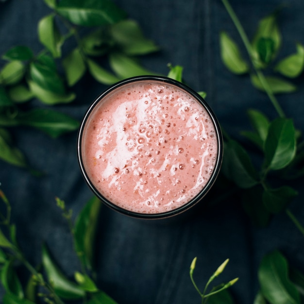 Top view pink smoothie next to leaves Free Photo