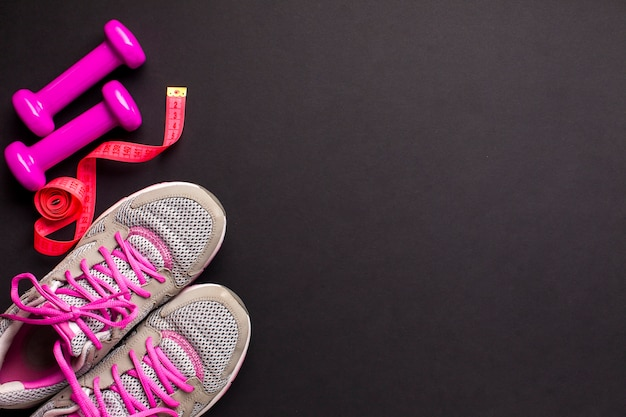 Top view pink sports attributes on dark background Free Photo