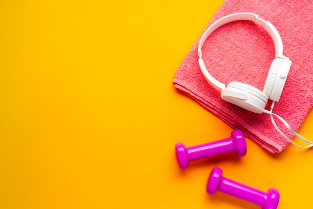 Top view pink towel and dumbbells on yellow background Free Photo