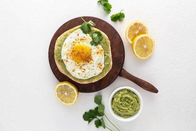 Vista dall'alto pita con crema di avocado e uovo fritto sul tagliere Foto Gratuite