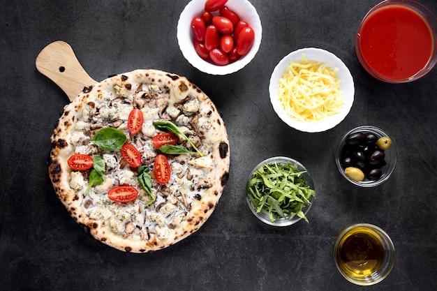 Вид сверху на пиццу и топпинги Бесплатные Фотографии