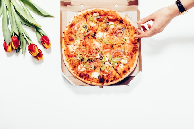 Top view of a pizza in a box, tulips and a female hand on a white background Premium Photo