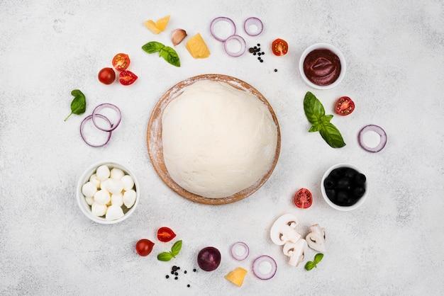 Вид сверху тесто для пиццы с овощами Premium Фотографии