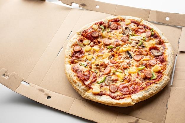茶色の箱の食べ物と食事の概念に関する上面ピザ Premium写真