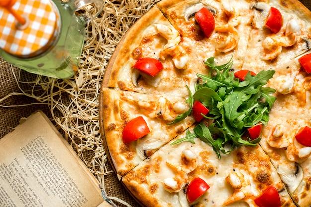 エビとキノコのトマトとルッコラとソフトドリンクの平面図ピザ 無料写真