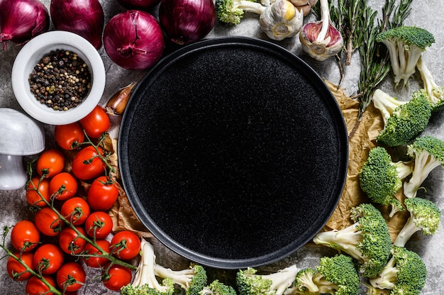 Top view of plate among uncooked vegetables. concept of home vegetarian cuisine Premium Photo
