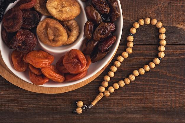 ドライフルーツの上面プレート、茶色の木製の背景に木製の数珠、イフタールの概念、ラマダン、イスラム教徒の休日 Premium写真
