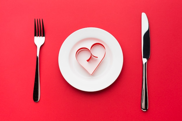 Top view of plate with paper heart shape and cutlery Free Photo