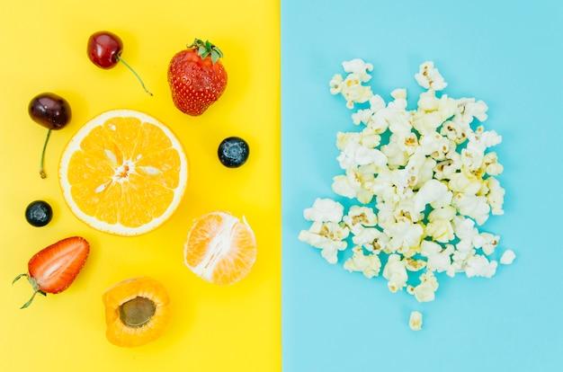 Top view pop corn vs fruit Free Photo