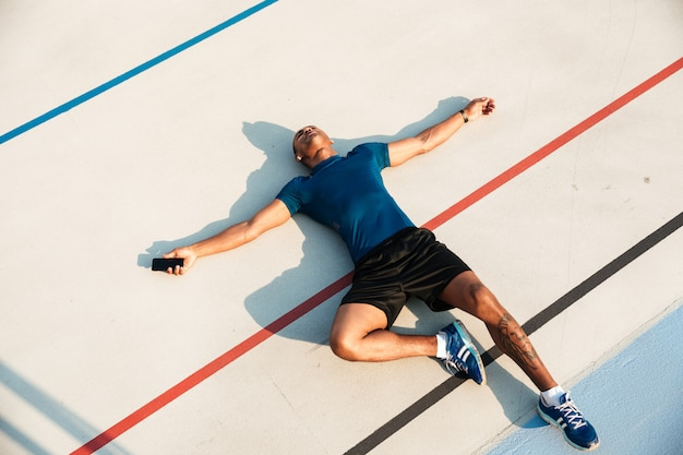 Top view portrait of a tired young african fitness man resting Free Photo