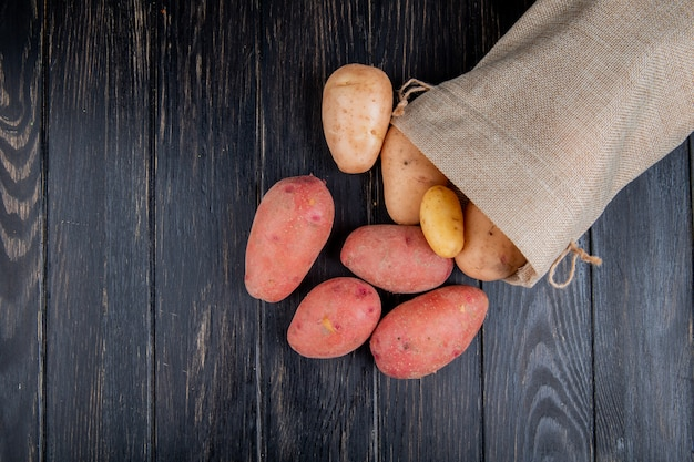 Top view of potatoes spilling out of sack on wood with copy space Free Photo