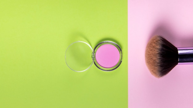 Top view of powder and brush on pink and green background Free Photo