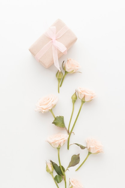 Vista dall'alto del presente con rose e nastro Foto Gratuite