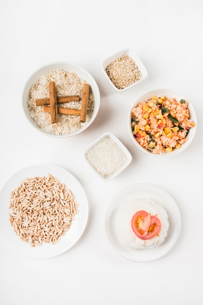 Top view of puffed rice; chinese fried rice and uncooked rice with cinnamon sticks Free Photo