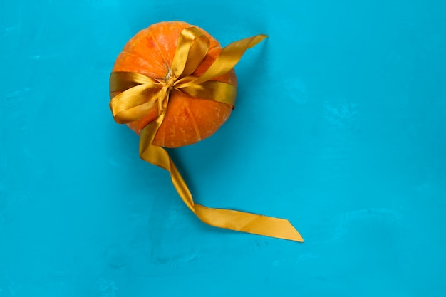 Top view pumpkin decorated golden satin ribbon on a blue background copy space Premium Photo