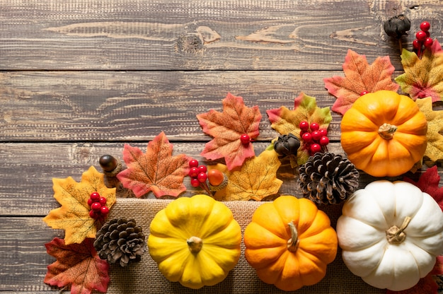 Top view of pumpkin, red berries, pine cones and autumn leaves Premium Photo