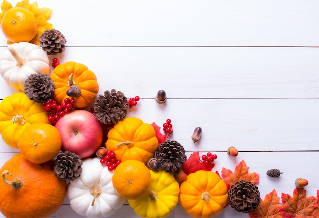Top view of pumpkins, red berries and pine cones Premium Photo