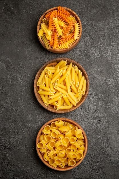 Vista dall'alto pasta italiana cruda diversa formata all'interno di piatti su grigio Foto Gratuite
