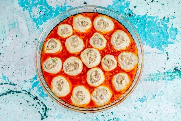 Вид сверху сырое мясное тесто, кусочки теста с фаршем внутри с томатным соусом внутри стеклянной сковороды на синем столе, тесто для еды, еды, мясного ужина Бесплатные Фотографии