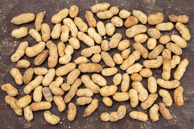 Top view raw nuts light colored and tasty on brown, nut walnut almond snack Free Photo