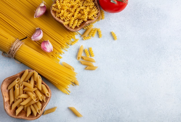 Top view of raw spaghetti with raw pasta in bowls with garlic and tomatoes on a gray surface Free Photo