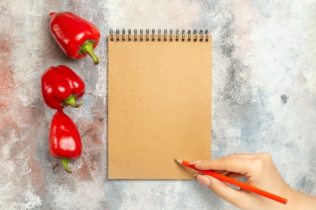 Top view red bell peppers a notebook red pencil in woman hand on nude surface free space Free Photo
