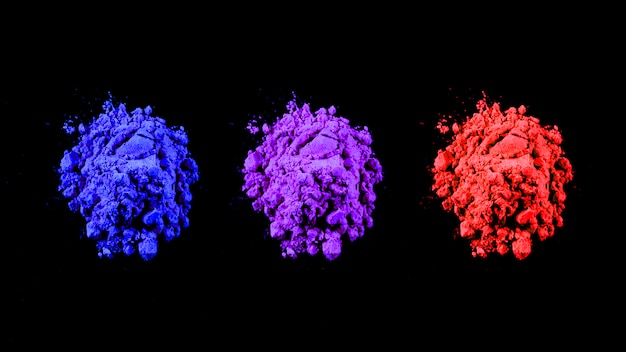 Top view of red,blue and purple holi colors arranged in row over black background Free Photo