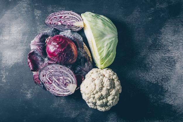 Top view red cabbage with cauliflower, sliced cabbage on dark textured background. horizontal Free Photo