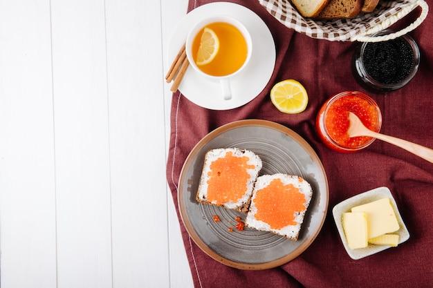 上面図赤キャビアトーストライ麦パンとカッテージチーズ赤キャビアバター黒キャビア白パンカップレモンシナモンスライスと白い背景のコピースペース 無料写真