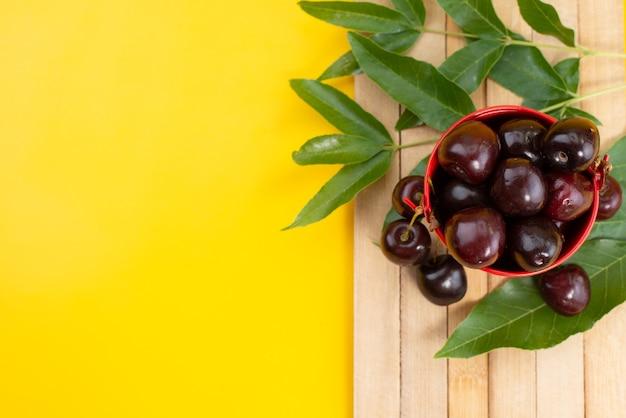 Un canestro interno morbido e succoso delle ciliege rosse di vista superiore sullo scrittorio di legno marrone e l'estate gialla di colore della frutta Foto Gratuite