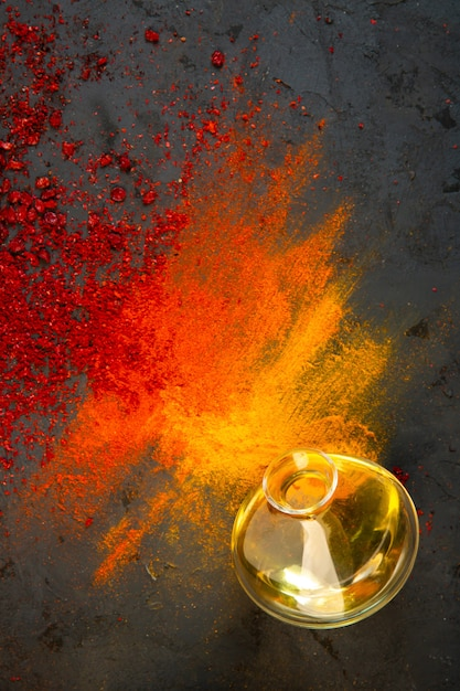 Top view of red chilli and sumac powder spices with curry and paprika and a bottle of olive oil Free Photo