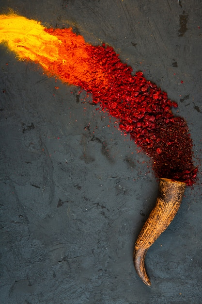 Top view of red chilli and sumac powder spices with curry scattered from a horn on black Free Photo