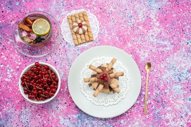 Вид сверху красная клюква с чаем и печеньем на фиолетовом фоне печенья с фруктовым сахаром Бесплатные Фотографии