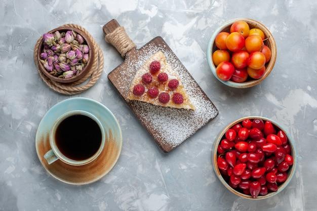 Vista dall'alto cornioli freschi rossi frutti aspri e deliziosi con torta e tè sulla scrivania leggera frutta fresca mellow acido Foto Gratuite